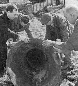 Rev. Stanley Evans helping workmen to move one of the old bells